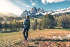 Γυναίκα με το σακίδιο πλάτης στην κοιλάδα βουνών στο ηλιοβασίλεμα την άνοιξη στοκ φωτογραφία με δικαίωμα ελεύθερης χρήσης