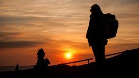 Γυναίκα με το σακίδιο πλάτης στο υπόβαθρο ηλιοβασιλέματος Στοκ Εικόνα