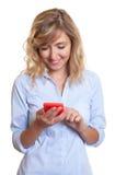 Γυναίκα με το σγουρό μήνυμα γραψίματος ξανθών μαλλιών με το τηλέφωνο Στοκ Εικόνες