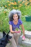 Γυναίκα με το σκυλί στον κήπο της Στοκ εικόνα με δικαίωμα ελεύθερης χρήσης