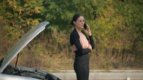 Γυναίκα με το σπασμένο αυτοκίνητο που καλεί τηλεφωνικώς απόθεμα βίντεο