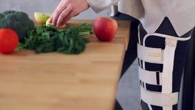 Γυναίκα με το σπασμένο μαγείρεμα ποδιών στην κουζίνα απόθεμα βίντεο
