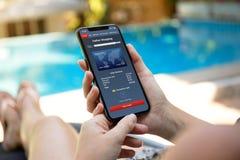 Γυναίκα με το τηλέφωνο εκμετάλλευσης λιμνών με app τις σε απευθείας σύνδεση αγορές Στοκ Φωτογραφίες