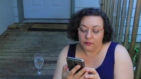 Γυναίκα με το τηλέφωνο στο μπροστινό μέρος απόθεμα βίντεο
