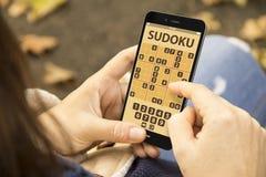 Γυναίκα με το τηλέφωνο εφαρμογής παιχνιδιών στο πάρκο Στοκ εικόνες με δικαίωμα ελεύθερης χρήσης