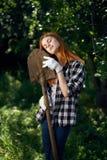 Γυναίκα με το φτυάρι, γυναίκα που κλίνει στο φτυάρι, γυναίκα στο φυτικό κήπο Στοκ Φωτογραφία