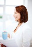 Γυναίκα με το φλιτζάνι του καφέ και τα έγγραφα Στοκ Εικόνες