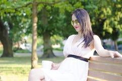 Γυναίκα με το φλιτζάνι του καφέ σε ένα πάρκο Στοκ Εικόνα