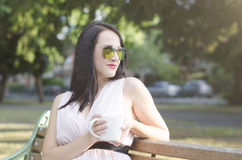 Γυναίκα με το φλιτζάνι του καφέ σε ένα πάρκο Στοκ εικόνα με δικαίωμα ελεύθερης χρήσης