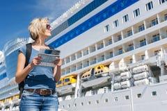 Γυναίκα με το χάρτη, μπροστά από το σκάφος της γραμμής κρουαζιέρας Στοκ Εικόνες