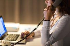 Γυναίκα με το lap-top που καλεί το τηλεφωνικό τη νύχτα γραφείο Στοκ Φωτογραφίες