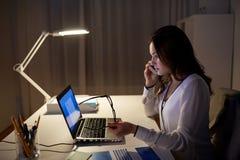 Γυναίκα με το lap-top που καλεί το smartphone στο γραφείο Στοκ εικόνα με δικαίωμα ελεύθερης χρήσης