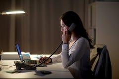 Γυναίκα με το lap-top που καλεί το τηλεφωνικό τη νύχτα γραφείο Στοκ φωτογραφία με δικαίωμα ελεύθερης χρήσης