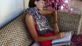 Γυναίκα με το lap-top που σκέφτεται και που κάνει τις σημειώσεις στο σημειωματάριο στο λεωφορείο έξω από τη βίλα Νησί του Μπαλί απόθεμα βίντεο