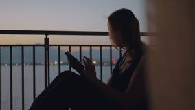 Γυναίκα με το PC ταμπλετών στο μπαλκόνι που αγνοεί τη θάλασσα απόθεμα βίντεο