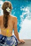Γυναίκα με το plumeria στη συνεδρίαση ξανθών μαλλιών εκτός από την πισίνα Στοκ φωτογραφία με δικαίωμα ελεύθερης χρήσης