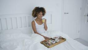 Γυναίκα με το smartphone στο κρεβάτι που έχει το γεύμα απόθεμα βίντεο