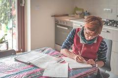 Γυναίκα με eyeglasses που κάθεται στον πίνακα, την ανάγνωση και τη γραφική εργασία και τα έγγραφα γραφής Εκλεκτική εστίαση, εγχώρ Στοκ φωτογραφία με δικαίωμα ελεύθερης χρήσης