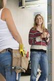 Γυναίκα με Toolbelt που μιλά στο χαμογελώντας θηλυκό στοκ εικόνες