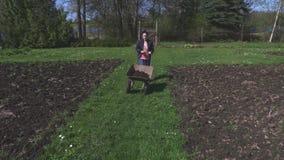 Γυναίκα με wheelbarrow στη χλόη φιλμ μικρού μήκους