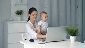 Γυναίκα μητέρων επιχειρηματιών με ένα μικρό παιδί που εργάζεται στον υπολογιστή φιλμ μικρού μήκους
