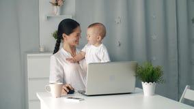 Γυναίκα μητέρων με ένα μικρό παιδί που εργάζεται στον υπολογιστή απόθεμα βίντεο