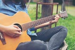 Γυναίκα μουσικών και η κιθάρα της στο πάρκο φύσης, κιθάρα πρακτικής στοκ φωτογραφία με δικαίωμα ελεύθερης χρήσης