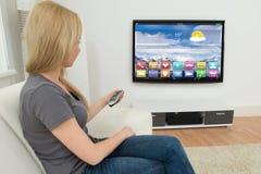 Γυναίκα μπροστά από την τηλεόραση με Apps Στοκ Εικόνα