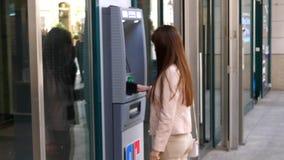Γυναίκα μπροστά από τη μηχανή του ATM απόθεμα βίντεο