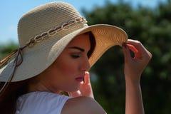 Γυναίκα μόδας στο άσπρο καπέλο φορεμάτων και γοητείας υπαίθρια στην ακτή ποταμών, βαθιά μπλε νερό στο υπόβαθρο Στοκ Φωτογραφίες