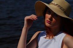 Γυναίκα μόδας στο άσπρο καπέλο φορεμάτων και γοητείας υπαίθρια στην ακτή ποταμών, βαθιά μπλε νερό στο υπόβαθρο Στοκ Εικόνες