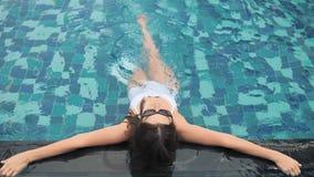 Γυναίκα μόδας στο άσπρο μαγιό που βρίσκεται στην πισίνα απόθεμα βίντεο