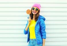 Γυναίκα μόδας πορτρέτου δροσερή χαμογελώντας αρκετά με το lollipop στα ζωηρόχρωμα ενδύματα πέρα από το άσπρο υπόβαθρο, που φορά έ Στοκ Εικόνα