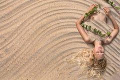 Γυναίκα μόδας που βρίσκεται στο υπόβαθρο άμμου παραλιών Στοκ Φωτογραφία