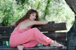 Γυναίκα μόδας στον πάγκο, με ένα ρόδινο ένδυμα κομματιού στοκ εικόνα