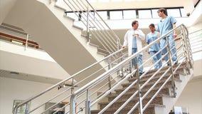 Γυναίκα νοσοκόμα που μιλά με έναν γιατρό και μια νοσοκόμα απόθεμα βίντεο