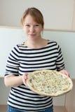 Γυναίκα ξανθών μαλλιών που φορά το ριγωτό πουκάμισο ναυτικών ` s που κρατά τη μεγάλη πίτσα στα χέρια και που εξετάζει τη κάμερα Στοκ Εικόνες
