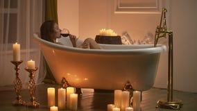 Γυναίκα ξαπλωμένη στο μπάνιο με το φως από τα κεριά για να χαλαρώσει και να πιει κρασί Ρομαντική χαλαρωτική αρωματική θεραπεία απόθεμα βίντεο