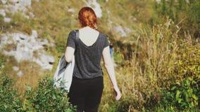 Γυναίκα οδοιπόρων με την κόκκινη τρίχα που περπατά μέσω του καταπληκτικού τοπίου άποψης βουνών στοκ εικόνες με δικαίωμα ελεύθερης χρήσης