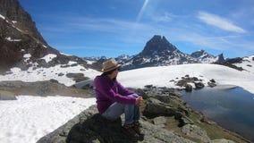 Γυναίκα οδοιπόρων που στηρίζεται και που φαίνεται το PIC du Midi Ossau στα γαλλικά βουνά των Πυρηναίων απόθεμα βίντεο