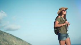 Γυναίκα οδοιπόρων που φορούν τα γυαλιά ηλίου και καπέλο που απολαμβάνει το καταπληκτικό τοπίο οδοιπορίας με τη θάλασσα και τα βου απόθεμα βίντεο