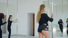 Γυναίκα ομάδα που τεντώνει το legsnear πυλώνα σε ένα στούντιο απόθεμα βίντεο