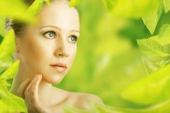 Γυναίκα ομορφιάς και μια φυσική φροντίδα δέρματος σε πράσινο Στοκ Φωτογραφίες