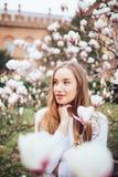 Γυναίκα ομορφιάς κοντά στο ρόδινο δέντρο magnolia στο άσπρο πουκάμισο, χέρια στο πηγούνι Άνοιξη στοκ φωτογραφία