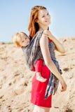 Γυναίκα ομορφιάς με ένα μωρό σε μια σφεντόνα μωρό mom Μητέρα και CH Στοκ Φωτογραφία