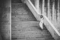 Γυναίκα ομορφιάς με μακρυμάλλη στα βήματα σκαλοπατιών Το κορίτσι ομορφιάς με τη γοητεία κοιτάζει στοκ εικόνα