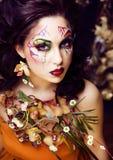 Γυναίκα ομορφιάς με την τέχνη και το κόσμημα προσώπου από τα clos ορχιδεών λουλουδιών Στοκ Εικόνες