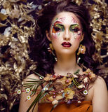Γυναίκα ομορφιάς με την τέχνη και το κόσμημα προσώπου από τις ορχιδέες λουλουδιών Στοκ Φωτογραφίες