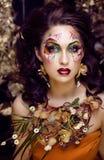 Γυναίκα ομορφιάς με την τέχνη και το κόσμημα προσώπου από τις ορχιδέες λουλουδιών Στοκ Εικόνες
