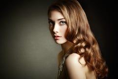Γυναίκα ομορφιάς με τη μακριά σγουρή τρίχα Όμορφο κορίτσι με το κομψό χ στοκ φωτογραφία με δικαίωμα ελεύθερης χρήσης